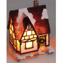 Leuchtendes Deko-Haus im winterlichen Stil weiße Fassade, rotes Dach
